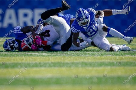 Georgia running back James Cook (4) is tackled by several Kentucky defenders during an NCAA college football game, in Lexington, Ky