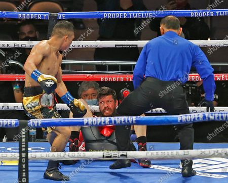 Issac Cruz, left, looks at Diego Magdaleno after knocking him down during the first round of their IBF lightweight boxing bout, in San Antonio