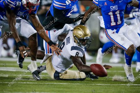 Navy quarterback Dalen Morris, center, fumbles the ball during the first half of an NCAA college football game, in Dallas. SMU defensive end Gary Wiley, left, would recover the ball on the play