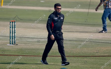 Stock Image of Pakistani umpire Aleem Dar walks back after receiving a souvenir on the record-breaking 210th ODI prior to the start of their 2nd one-day international cricket match between Pakistan and Zimbabwe at the Pindi Cricket Stadium, in Rawalpindi, Pakistan, . Dar achieved the record-breaking 210th ODI as the 52-year-old surpassed South Africa's Rudi Koertzen's record of supervising in most one-day internationals