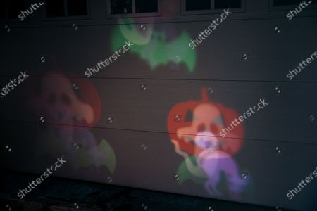 """Stock Picture of Projections of ghosts, bats, cats, and jack-o-lanterns dance across the garage door of a couple's home during Oakwood's first """"COVID-19 Halloween"""".Normally, Volusia anticipates hundreds of trick-or-treaters but during the first """"COVID-19 Halloween"""" in America, parents played it safe, families wore masks with their costumes and parents ensured that their children did not take off their masks or get too close to those they did not know due to coronavirus fears. Many opted out of the festivities altogether, but those who ventured out were met with buckets full of candy and kind-hearted but distanced waves from neighbors."""