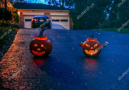 """Two jack-o-lanterns glow on a driveway as the sun sets during Oakwood's first """"COVID-19 Halloween"""".Normally, Volusia anticipates hundreds of trick-or-treaters but during the first """"COVID-19 Halloween"""" in America, parents played it safe, families wore masks with their costumes and parents ensured that their children did not take off their masks or get too close to those they did not know due to coronavirus fears. Many opted out of the festivities altogether, but those who ventured out were met with buckets full of candy and kind-hearted but distanced waves from neighbors."""