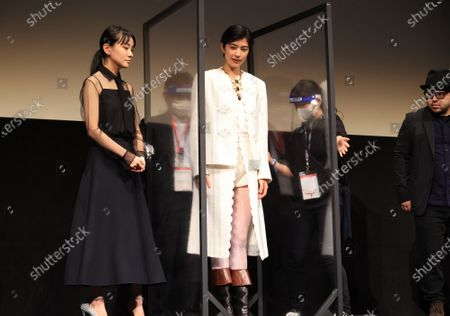 """Movie festival officials set partitions to keep distance as (L-R) Japanese actresseses Nao, Yui Sakuma and film director Ryohei Yoshino pose for photo as they attend the world premiere of their movie """"Eternally Younger Than Those Idiots"""" for the Tokyo International Film Festival (TIFF) in Tokyo on Sunday, November 1, 2020."""
