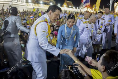King Maha Vajiralongkorn, center left and and Princess Sirivannavari Nariratana, center right, greet supporters in Bangkok, Thailand, . Under increasing pressure from protesters demanding reforms to the monarchy, Thailand's king and queen met Sunday with thousands of adoring supporters in Bangkok, mixing with citizens in the street after attending a religious ceremony inside the Grand Palace
