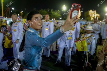 Thai Princess Sirivannavari Nariratana take a selfie as the royal family meets their supporters in Bangkok, Thailand, . Under increasing pressure from protesters demanding reforms to the monarchy, Thailand's king and queen met Sunday with thousands of adoring supporters in Bangkok, mixing with citizens in the street after attending a religious ceremony inside the Grand Palace