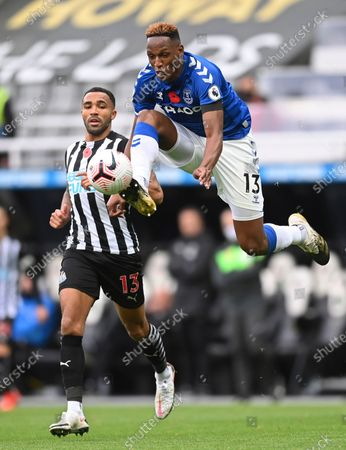 Everton's Yerry Mina, right, jumps to control the ball by Newcastle's Callum Wilson during an English Premier League soccer match between Newcastle United and Everton at the St. James' Park stadium in Newcastle, England