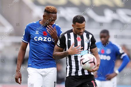 Everton's Yerry Mina, left says something to Newcastle's Callum Wilson just before Wilson was about to take a penalty kick during an English Premier League soccer match between Newcastle United and Everton at the St. James' Park stadium in Newcastle, England