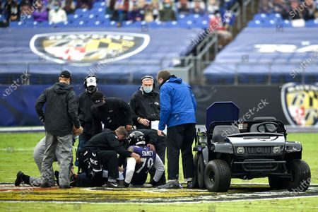Stock Photo of Trainers tend to Baltimore Ravens offensive tackle Ronnie Stanley (79) during the first half of an NFL football game against the Pittsburgh Steelers, in Baltimore