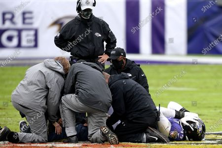 Trainers tend to Baltimore Ravens offensive tackle Ronnie Stanley, right, during the first half of an NFL football game against the Pittsburgh Steelers, in Baltimore