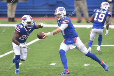 Stock Image of Buffalo Bills quarterback Josh Allen, center, hands off to Buffalo Bills' Devin Singletary, left, during the first half of an NFL football game against the New England Patriots, in Orchard Park, N.Y