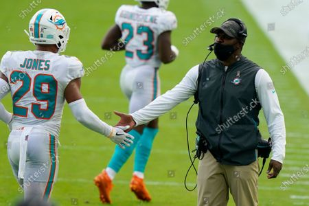 Miami Dolphins head coach Brian Flores greets free safety Brandon Jones (29) after a play, during the second half of an NFL football game against the Los Angeles Rams, in Miami Gardens, Fla