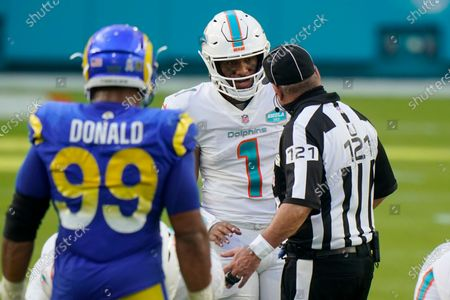 Miami Dolphins quarterback Tua Tagovailoa (1) talks to umpire Paul King (121), during the second half of an NFL football game against the Los Angeles Rams, in Miami Gardens, Fla
