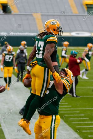 Green Bay Packers' Davante Adams is congrtaultaed by Lucas Patrick cafter catching a touchdown pass during the first half of an NFL football game against the Minnesota Vikings, in Green Bay, Wis