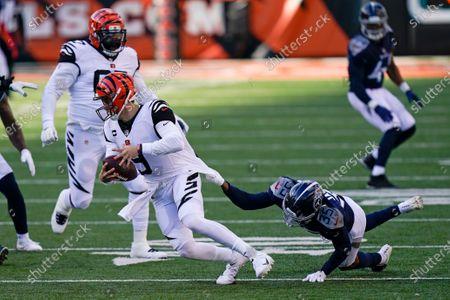 Cincinnati Bengals quarterback Joe Burrow (9) runs against Tennessee Titans' Chris Jackson (35) during the second half of an NFL football game, in Cincinnati