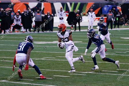 Cincinnati Bengals' Tyler Boyd (83) runs against Tennessee Titans' Kevin Byard (31) and Chris Jackson (35) during the second half of an NFL football game, in Cincinnati