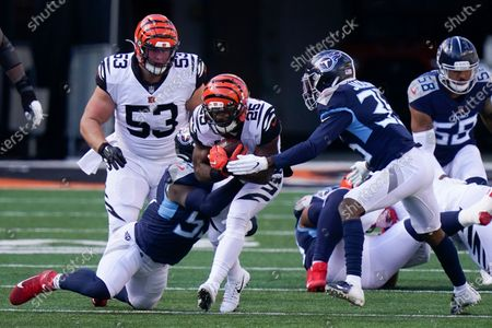 Cincinnati Bengals' Giovani Bernard (25) is tackled by Tennessee Titans' Jayon Brown (55) and Chris Jackson (35) during the first half of an NFL football game, in Cincinnati