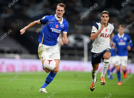 Brighton's Dan Burn, left, and Tottenham's Erik Lamela chase after the ball during the English Premier League soccer match between Tottenham Hotspur and Brighton & Hove Albion at Tottenham Hotspur Stadium, London