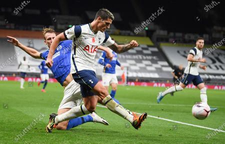 Stock Picture of Tottenham's Erik Lamela kicks the ball as Brighton's Dan Burn attempts a tackle during the English Premier League soccer match between Tottenham Hotspur and Brighton & Hove Albion at Tottenham Hotspur Stadium, London
