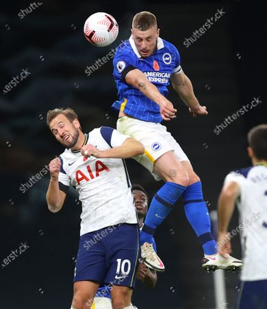 Brighton's Adam Webster leaps above Tottenham's Harry Kane to head the ball during the English Premier League soccer match between Tottenham Hotspur and Brighton & Hove Albion at Tottenham Hotspur Stadium, London