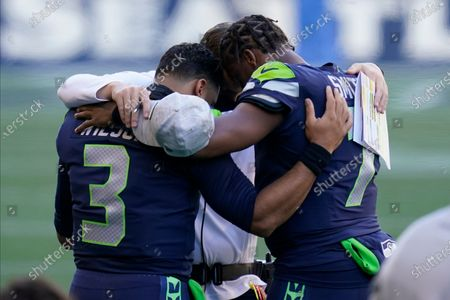 Seattle Seahawks quarterbacks Russell Wilson (3) and Geno Smith, right, huddle with a team personnel member during the national anthem before an NFL football game against the San Francisco 49ers, in Seattle