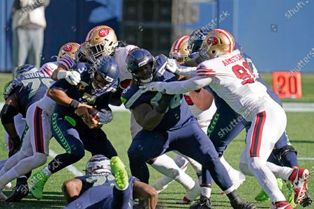 Seattle Seahawks quarterback Russell Wilson, left, is tackled as offensive guard Damien Lewis, right, blocks San Francisco 49ers defensive end Arik Armstead (91) during the first half of an NFL football game, in Seattle