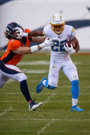 Los Angeles Chargers running back Justin Jackson (22) stiff-arms Denver Broncos linebacker Anthony Chickillo (91) while running with the football during the first half of an NFL football game, in Denver