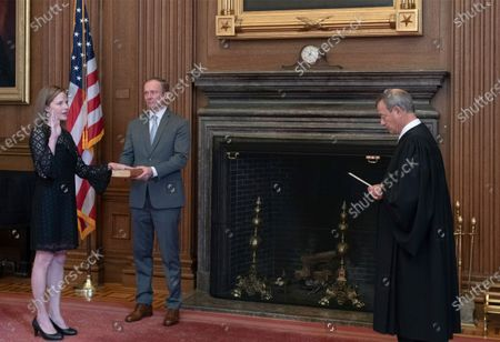 In this photo released by the United States Supreme Court, Chief Justice of the US John G. Roberts, Jr., administers the Judicial Oath to Judge Amy Coney Barrett in the East Conference Room, Supreme Court Building in Washington, DC. Judge Barrett's husband, Jesse M. Barrett, holds the Bible. Mandatory