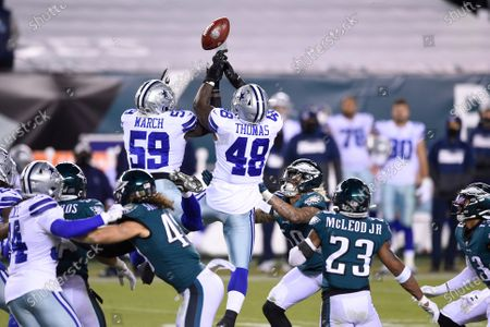 Dallas Cowboys' Justin March (59) and Joe Thomas (48) leap to try and catch a kick during the second half of an NFL football game against the Philadelphia Eagles, in Philadelphia