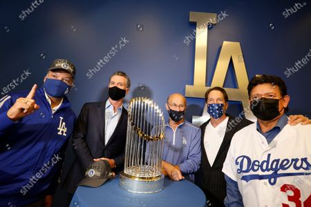 Los Angeles, California-Oct. 30, 2020-Gov. Gavin Newsom, second from left, takes pictures with CA Secretary of State Alex Padilla, left, Dodger president/CEO Stan Kasten, center, Dodger owner Peter Guber, second from right, and former Dodger pitcher Fernando Valenzuela, right, with the World Series trophy at Dodger Stadium on Oct. 30, 2020.