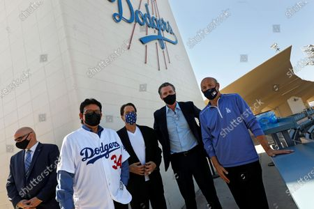 Los Angeles, California-Oct. 30, 2020-Gov. Gavin Newsom , second from right, takes pictures with former Dodger pitcher Fernando Valenzuela, second from left, Dodger owner Peter Guber, third from left, and Dodger president/CEO Stan Kasten, right, at Dodger Stadium on Oct. 30, 2020
