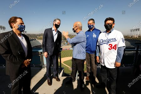 Los Angeles, California-Oct. 30, 2020-Gov. Gavin Newsom, second from left, visits Dodger Stadium with Dodger owner Peter Guber, left, Dodger president/CEO Stan Kasten, center, CA Secretary of State Alex Padilla, second from right, and former Dodger pitcher Fernando Valenzuela, right, on Oct. 30, 2020.