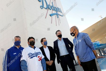 Los Angeles, California-Oct. 30, 2020-Gov. Gavin Newsom, second from right, takes pictures with CA Secretary of State Alex Padilla, left, former Dodger pitcher Fernando Valenzuela, second from left, Dodger owner Peter Guber, third from left, and Dodger president/CEO Stan Kasten, right, at Dodger Stadium on Oct. 30, 2020.