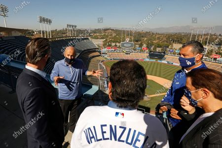 Los Angeles, California-Oct. 30, 2020-Gov. Gavin Newsom, left, visits Dodger Stadium with Dodger president/CEO Stan Kasten, CA Secretary of State Alex Padilla, second from right, Dodger owner Peter Guber, right, and and former Dodger pitcher Fernando Valenzuela, back to camera, on Oct. 30, 2020..