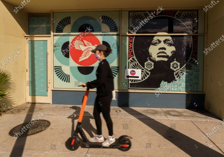 Stock Picture of Person in a scooter drives past the image of civil rights activist Angela Davis by Los Angeles street artist Shepard Fairey, decorating the Hollywood Pantages Theatre, an official in-person center voting center in Los Angeles Inglewood, Calif., . California mailed ballots to all active registered voters this year, and more than 8.7 million have already been returned. That's nearly 60% of all votes cast in the 2016 presidential election in California
