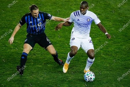 Orlando City defender Kamal Miller, right, and Montreal Impact midfielder Samuel Piette battle for the ball during their MLS soccer match, at Red BullArena in Harrison, NJ