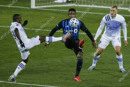 Orlando City midfielder Sebastian Mendez, left, and Montreal Impact attacker Romell Quioto battle for the ball during their MLS match, at Red BullArena in Harrison, NJ