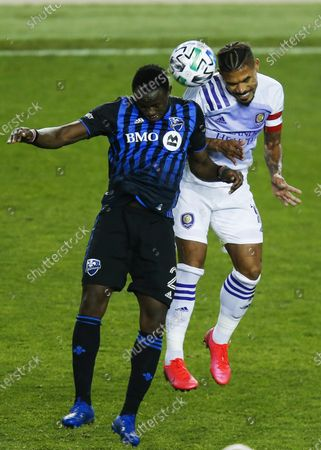Stock Image of Orlando City midfielder Junior Urso, right, and Montreal Impact midfielder Victor Wanyama battle for the ball during their MLS match, at Red BullArena in Harrison, NJ