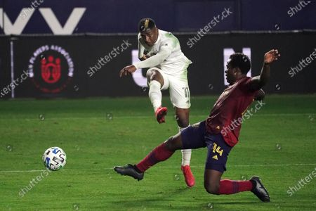 Los Angeles Galaxy's Yony Gonzalez, center, shoots under pressure by Real Salt Lake's Nedum Onuoha during the first half of an MLS soccer match, in Carson, Calif