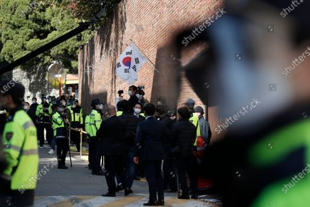 South Korean police officers stand outside a residence of former President Lee Myung-bak in Seoul, South Korea, . Lee was sent back to prison on Monday, four days after the country's top court upheld a 17-year prison term on him over corruption crimes