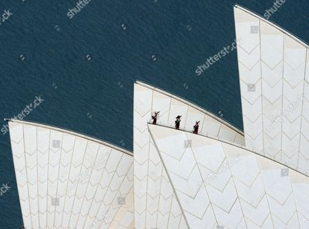 Royal Highland Fusilier Christopher Mitchell, Lance Corporal Ryan Gonsales of Black Watch and Corporal Stuart Gillies of the Royal Highland Fusiliers playing the bagpipes on top of the Sydney Opera House