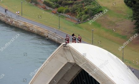 Stock Picture of Royal Highland Fusilier Christopher Mitchell, Lance Corporal Ryan Gonsales of Black Watch and Corporal Stuart Gillies of the Royal Highland Fusiliers playing the bagpipes on top of the Sydney Opera House