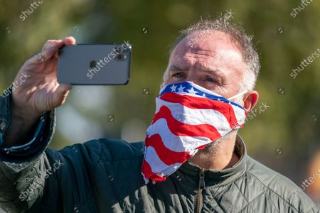 Chef Jose Andres, founder of the World Central Kitchen, uses his phone as he attends an event to draw attention to Americans who have died during the COVID-19 pandemic, in Washington