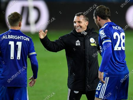 Leicester's manager Brendan Rodgers smiles as he shakes hands with his players Leicester's Marc Albrighton,left and Leicester's Christian Fuchs after the end of the English Premier League soccer match between Leeds United and Leicester City at Elland Road in Leeds, England, . Leicester won the game 4-1