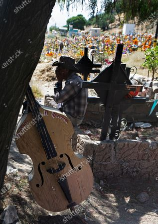 Musician rests on a grave at the Valle de Chalco Municipal Cemetery were families come to mark Day of the Dead on the outskirts of Mexico City, Mexico City, on . Mexico's Day of the Dead celebration isn't the same in a year so marked by death after more than 90,000 people have died of COVID-19