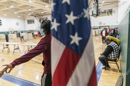 Stock Photo of Moe Jackson holds the hand of his girlfriend, Gabrielle McCoy, left, while waiting in line to fill out a ballot on the last day of early absentee voting before tomorrow's general election at the Northwest Activities Center in Detroit