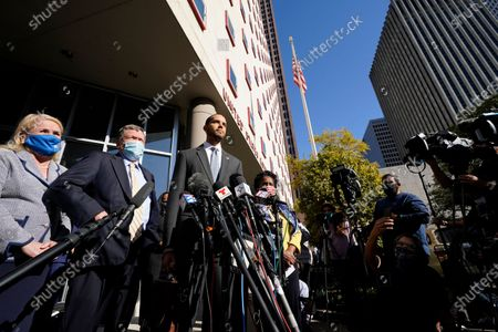 Harris County Clerk Chris Hollins, center, speaks outside the federal courthouse after a hearing, in Houston. A federal judge has rejected a last-ditch Republican effort to invalidate nearly 127,000 votes in Houston. U.S. District Judge Andrew Hanen's ruling Monday concerned ballots cast at drive-thru polling centers that were established during the pandemic. The lawsuit was brought by conservative Texas activists who have railed against expanded voting access in Harris County