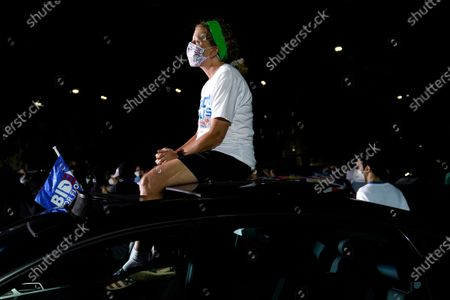 Stock Image of Rep. Debbie Wasserman Schultz, D-Fla., listens from the roof of her car as former President Barack Obama speaks at a rally as he campaigns for Democratic presidential candidate former Vice President Joe Biden, in Miami