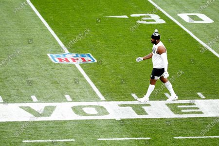 """Las Vegas Raiders defensive tackle Johnathan Hankins (90) walks past a stencil of the word """"vote"""" during warmups prior to the start of an NFL football game against the Cleveland Browns, in Cleveland"""