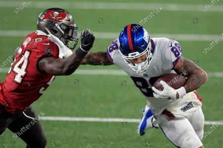 New York Giants' Evan Engram, right, fends off Tampa Bay Buccaneers' Lavonte David during the first half of an NFL football game, in East Rutherford, N.J