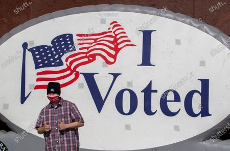 Anthony Robles, of Garden Grove, poses as his sister, Daniela Robles, not pictured, takes a photo of him after voting early at the Honda Center on Monday, Nov. 2, 2020 in Anaheim, CA. (Allen J. Schaben / Los Angeles Times)